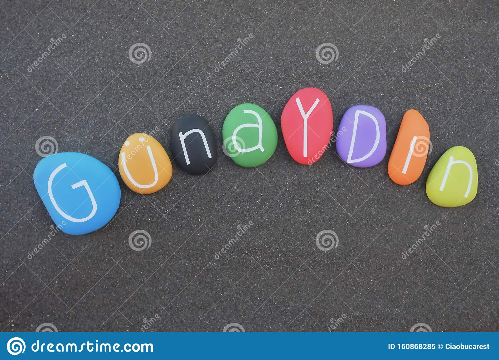 Günaydın, Good morning in turkish language composed with multicolored stone letters over black volcanic sand