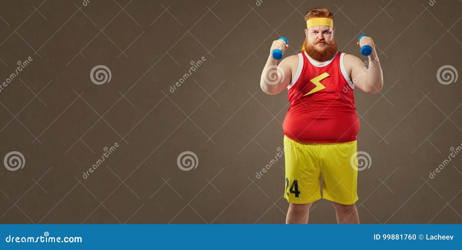 Gęsty śmieszny facet w sportswear z małymi dumbbells