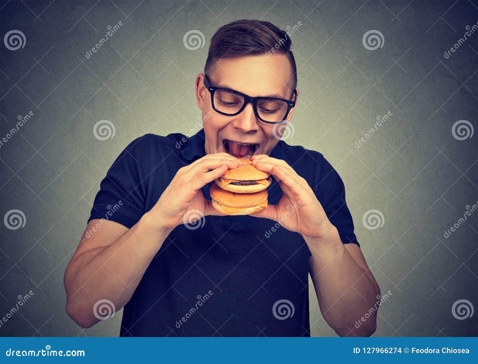 Głodny mężczyzna ma dwoistego hamburger