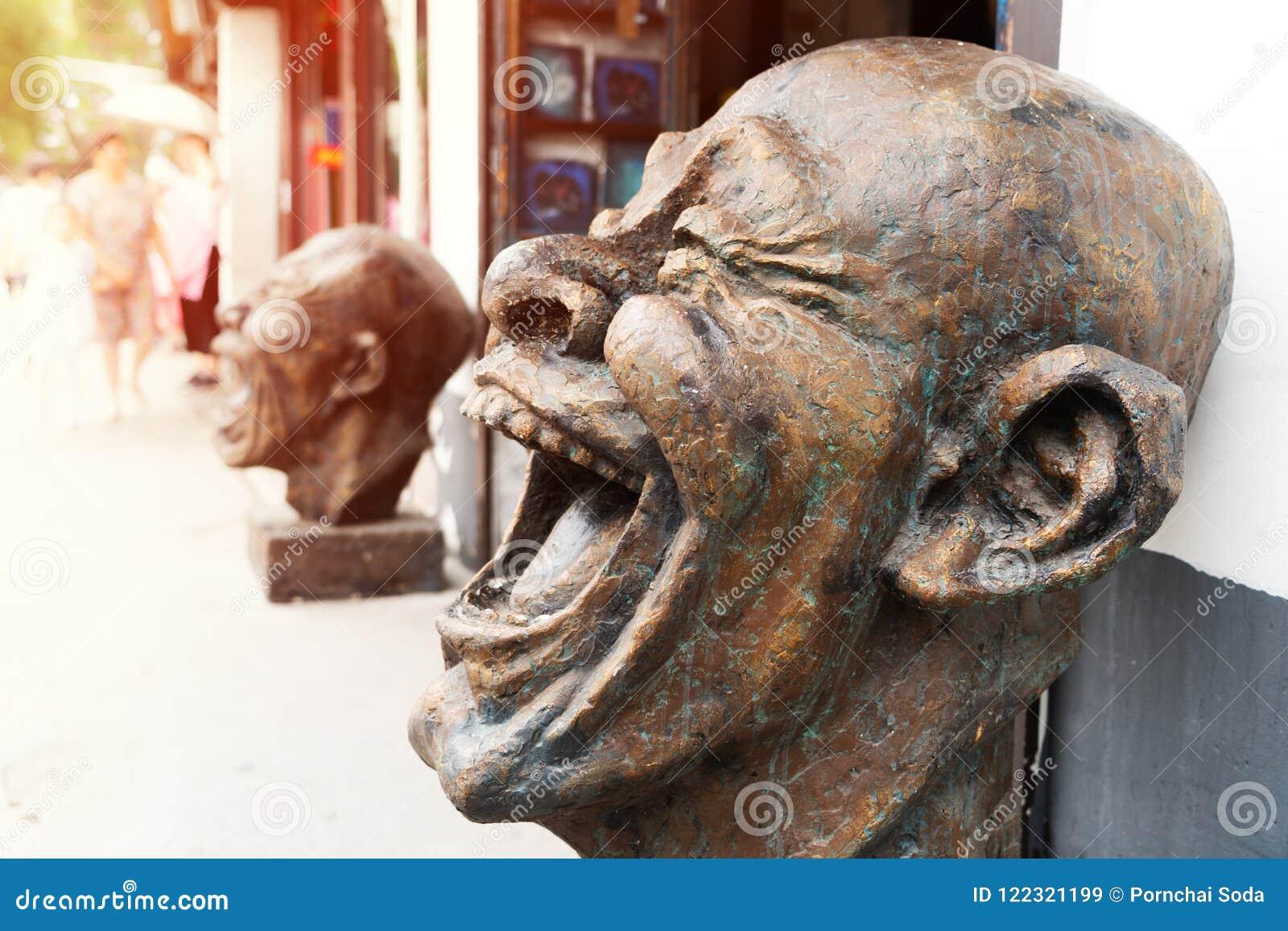 Głowa śmiechu brązu statuy, śmieszna kierownicza rzeźba