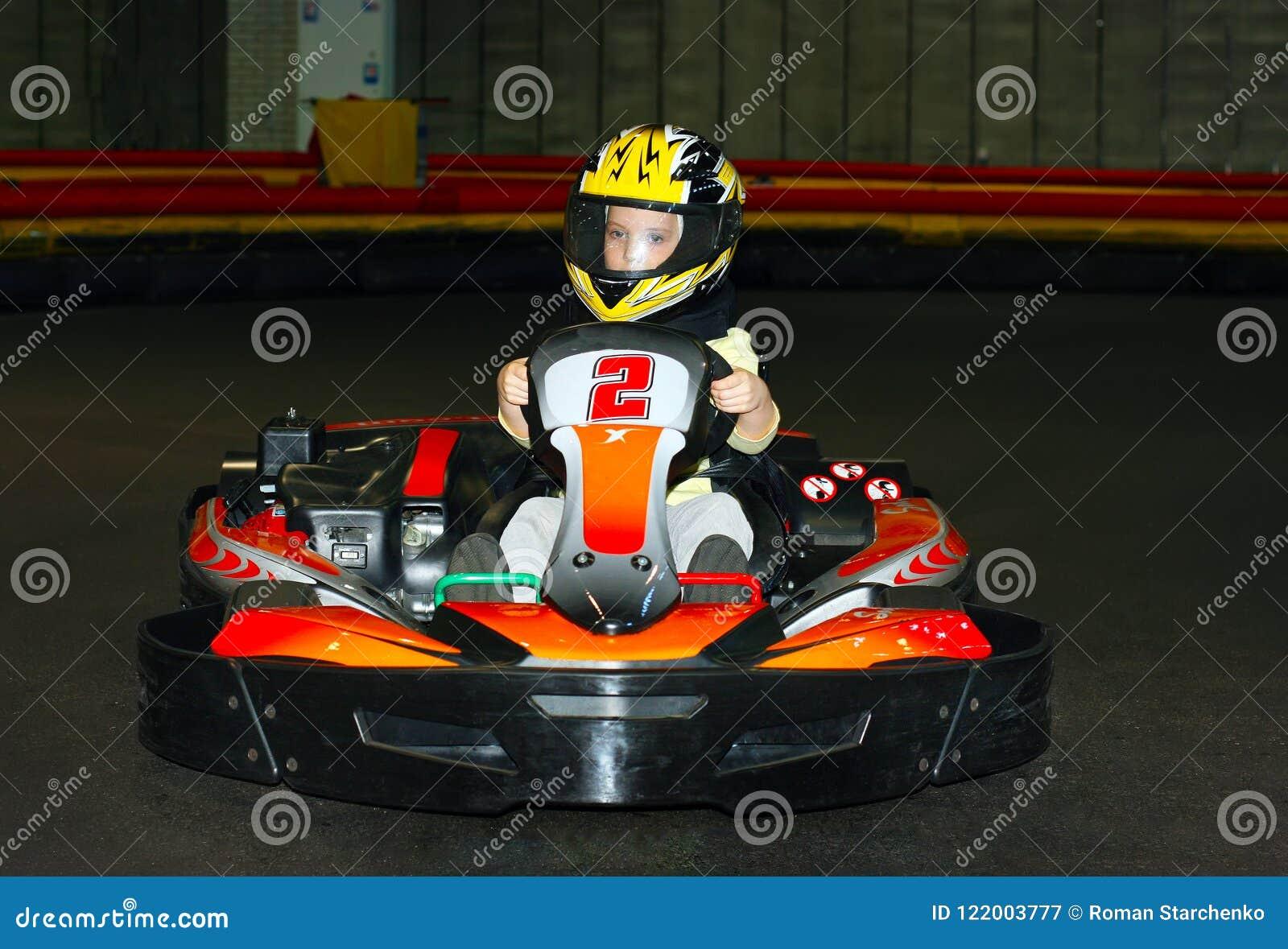 Gaat -gaan-kart het glimlachende meisje in een helm in op het karting spoor