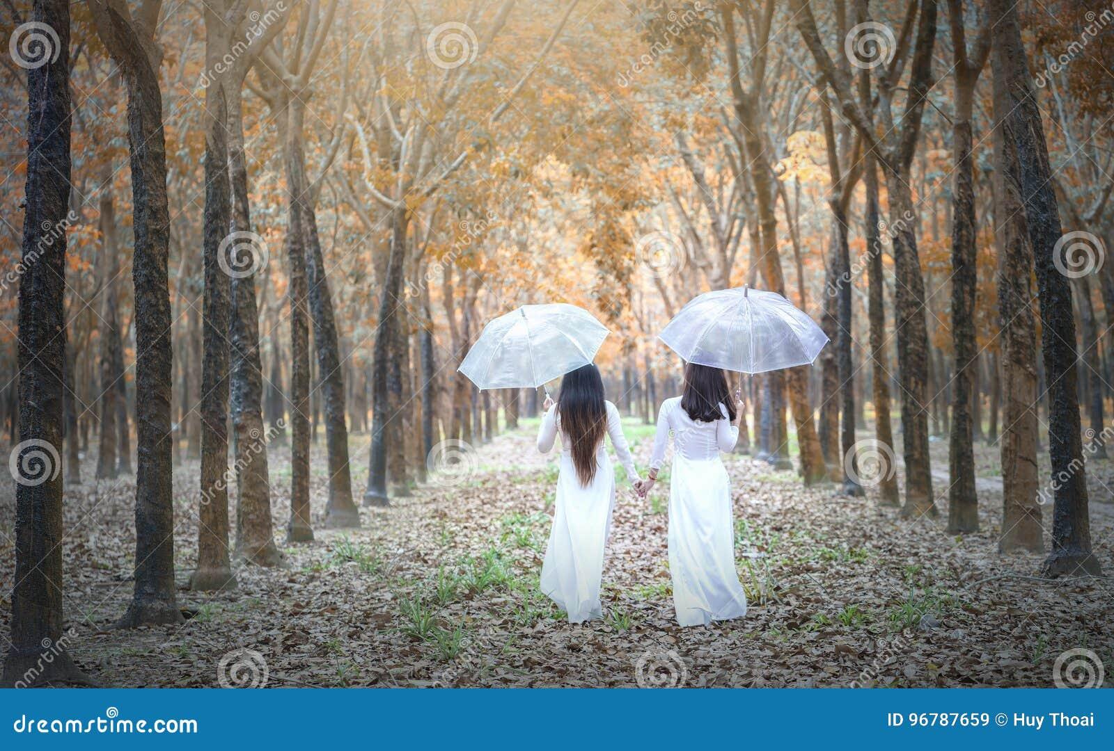 Gaat Vietnamees meisje twee in traditionele lange kleding of Ao Dai naar het eind van de weg in rubberbos