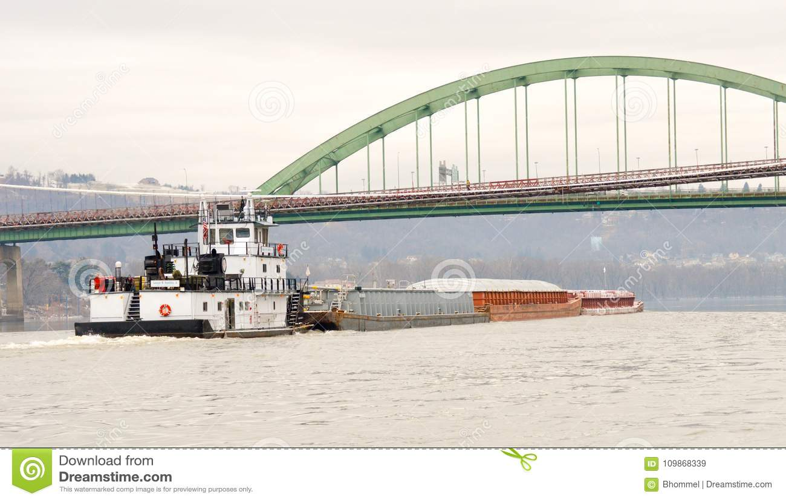 Gabarra del carbón que va abajo del río Ohio debajo de un puente