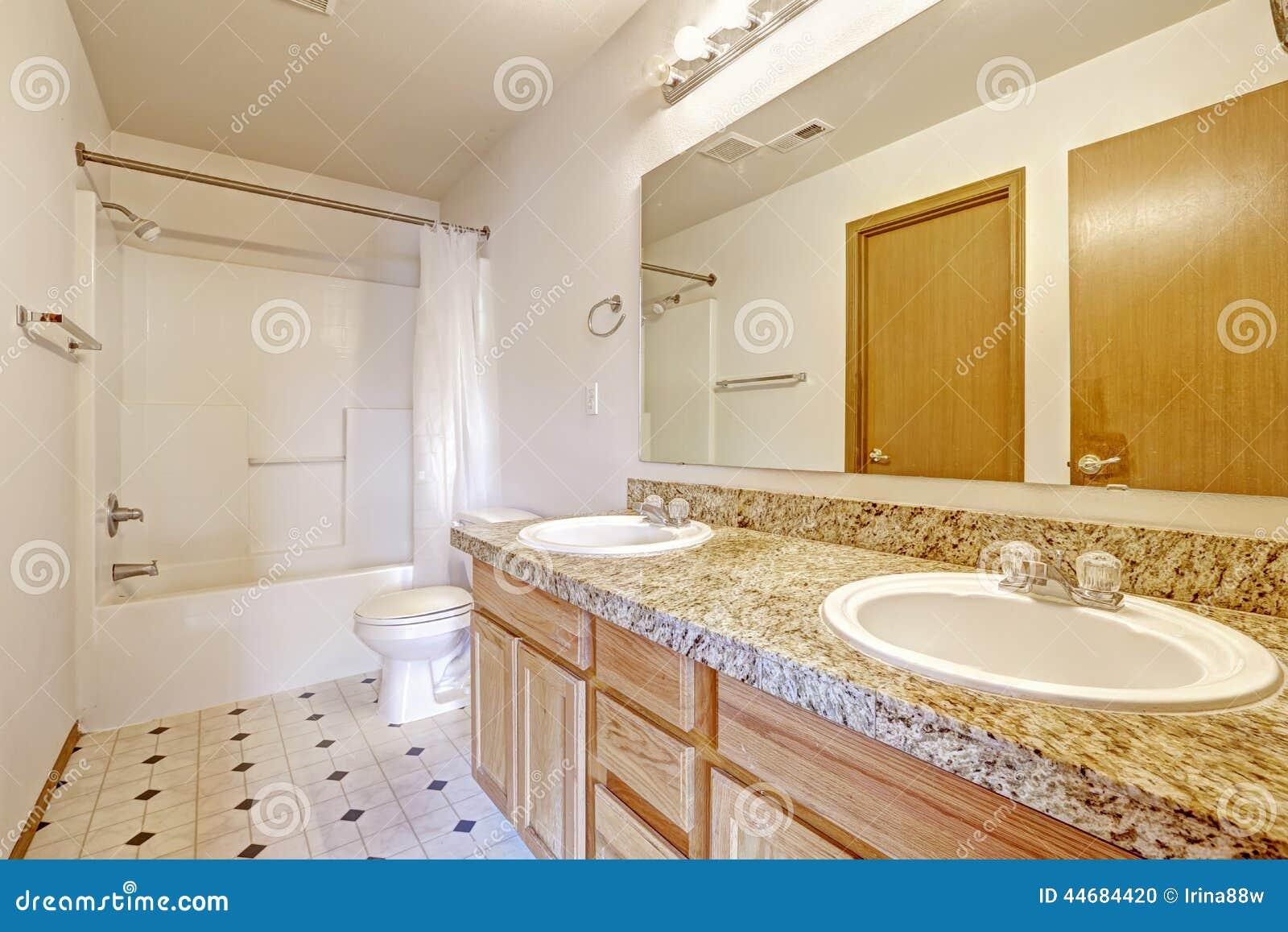 gabinetto di bagno con la cima del granito due lavandini e lo specchio
