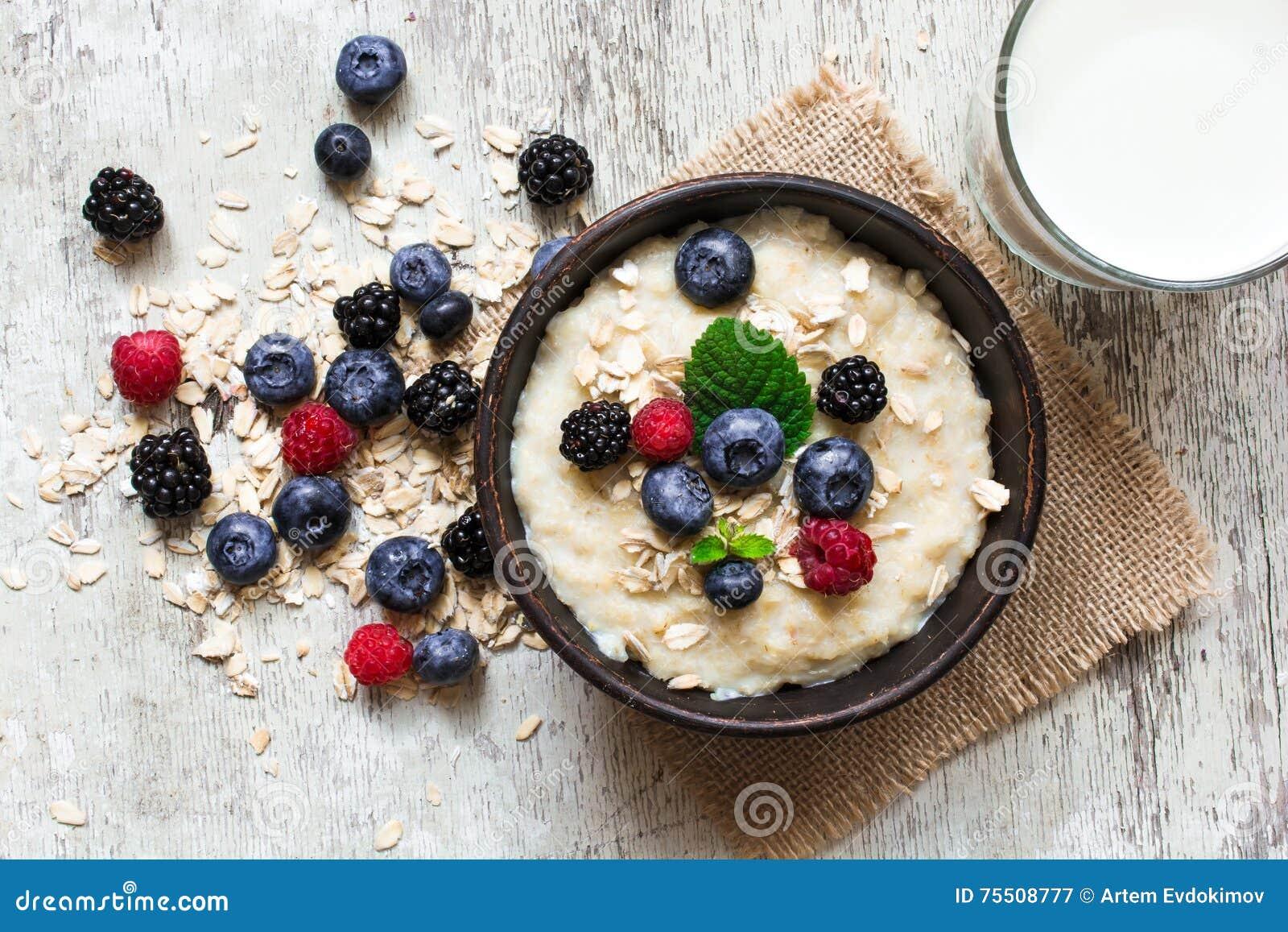 Gachas de avena sanas de la harina de avena del desayuno en un cuenco con el vidrio de leche