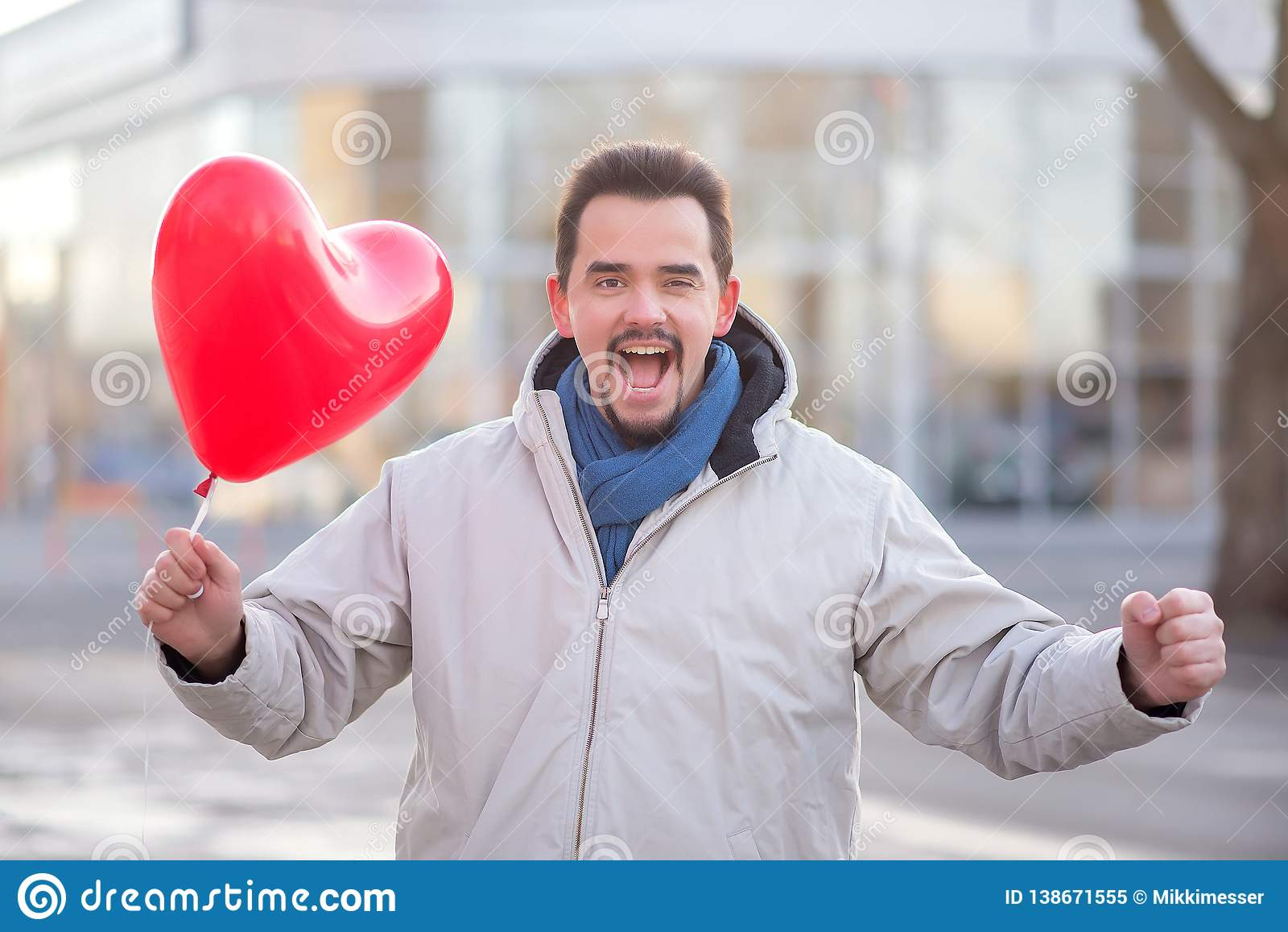 Gaf de gelukkig lachende knappe mens met een rood hart luchtimpuls gestalte die zich in een stadsstraat bevinden