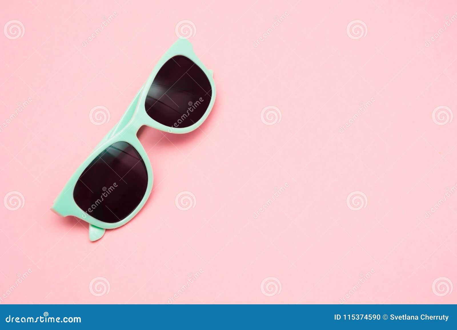 Gafas de sol en colores pastel verdes aisladas en la visión rosada, superior dinámica Copie el espacio Concepto del verano