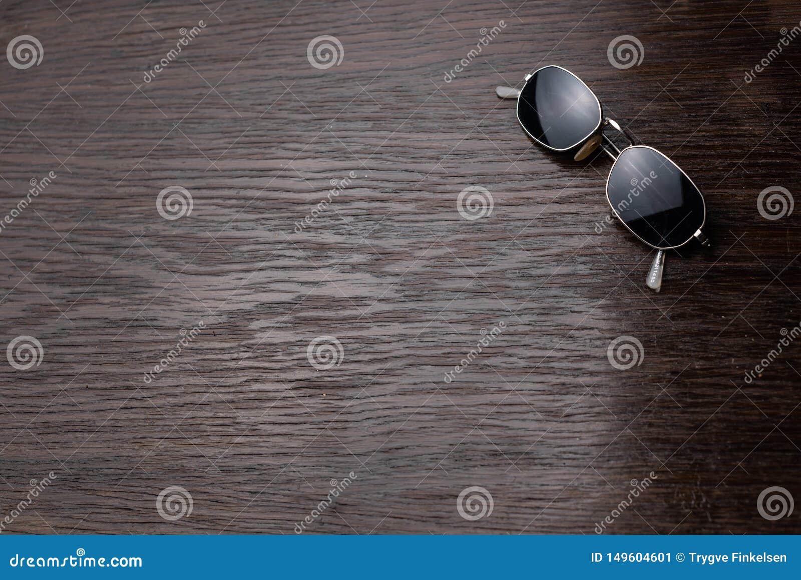 Gafas de sol en una tabla de madera oscura