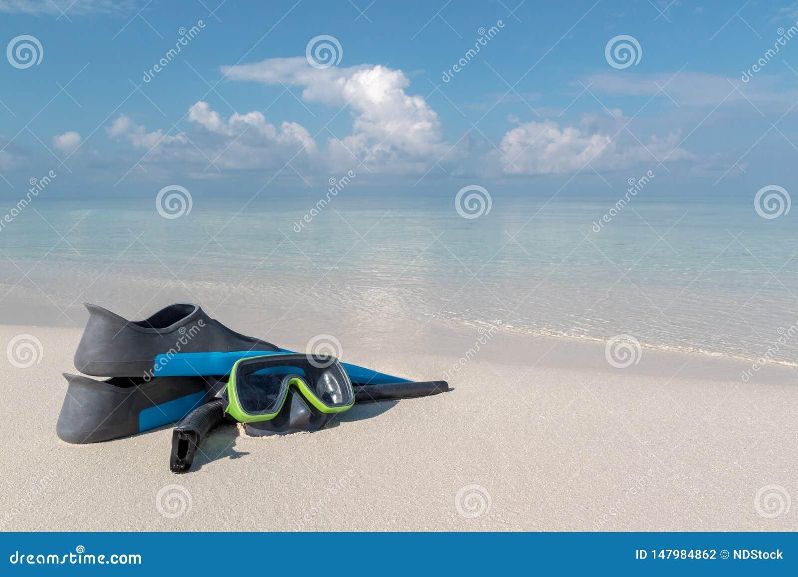 Gafas y aletas del equipo de submarinismo en una playa blanca Agua azul clara como fondo