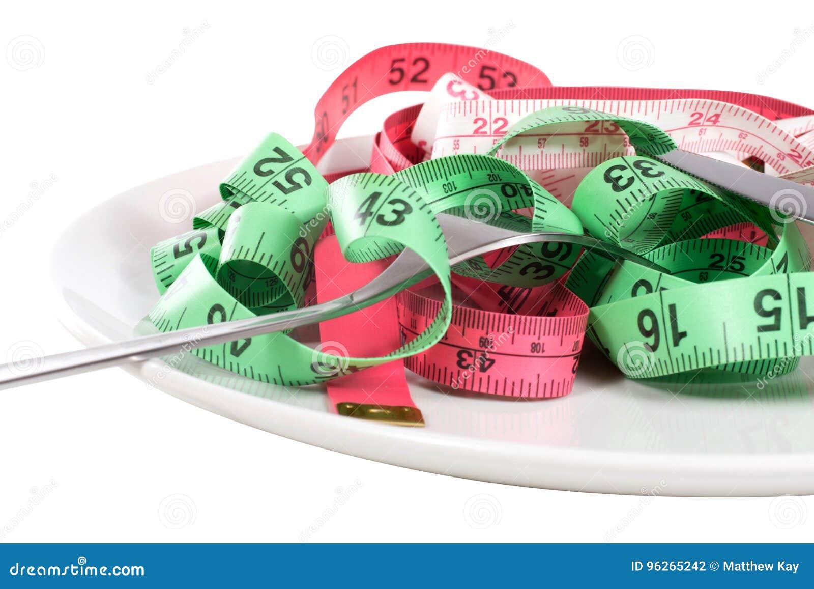 Gaffel och måttband i ett begrepp för viktförlust