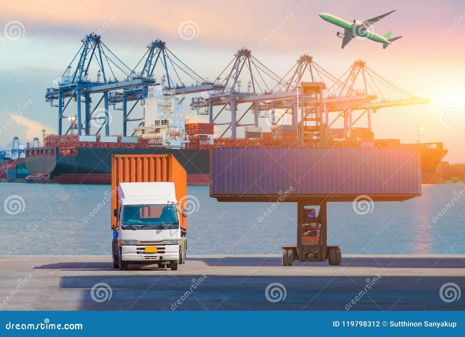 Gaffeltrucklyftande lastbehållare i sändande gård eller skeppsdockagård mot soluppgånghimmel för trans.import, export och journal