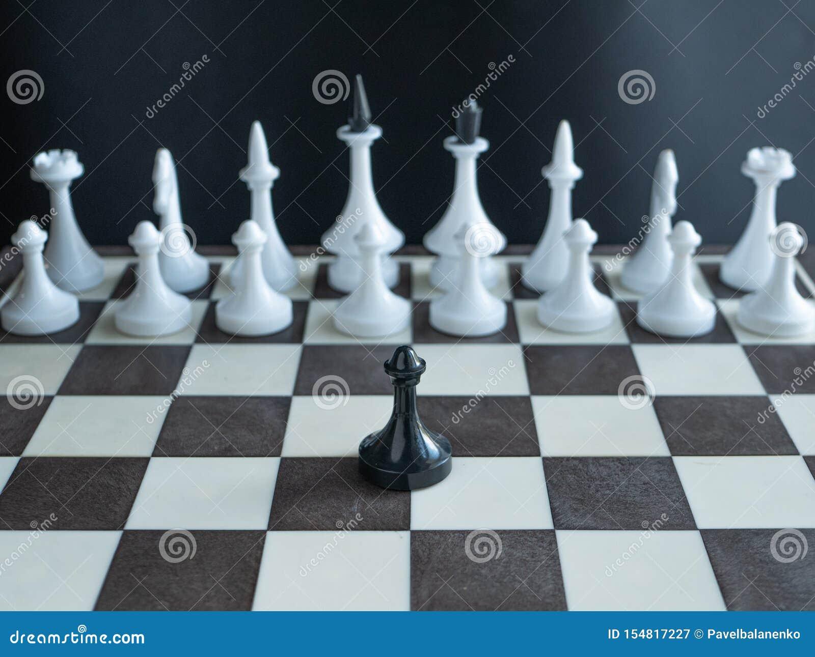 Gage noir isolé seul se tenant contre l armée entière des figures blanches sur l échiquier le concept dépeignent une armée Martin