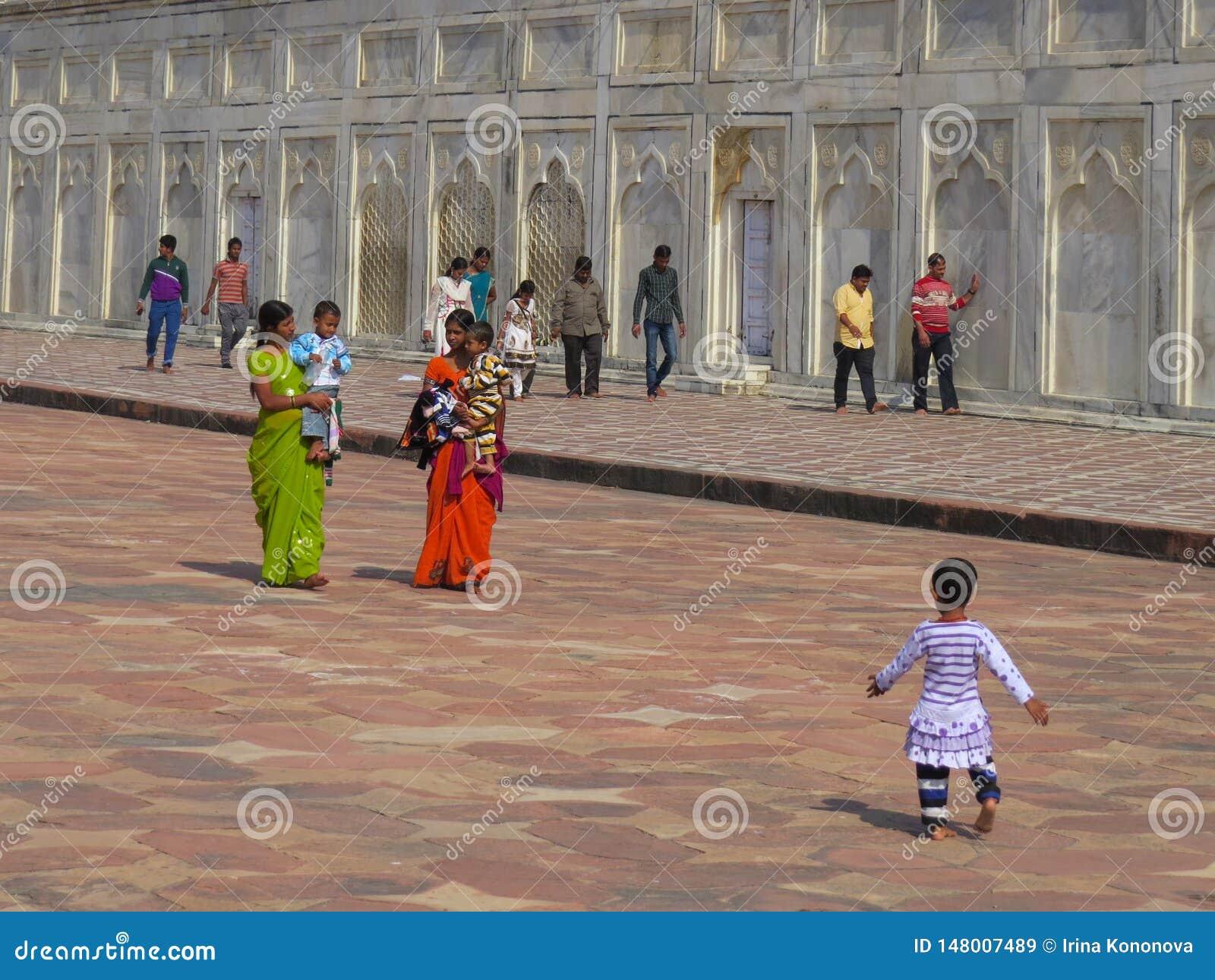 Gagra Indien, November 21, 2013 Indiska mödrar i sari med barn och andra personer nära väggarna av Taj Mahal