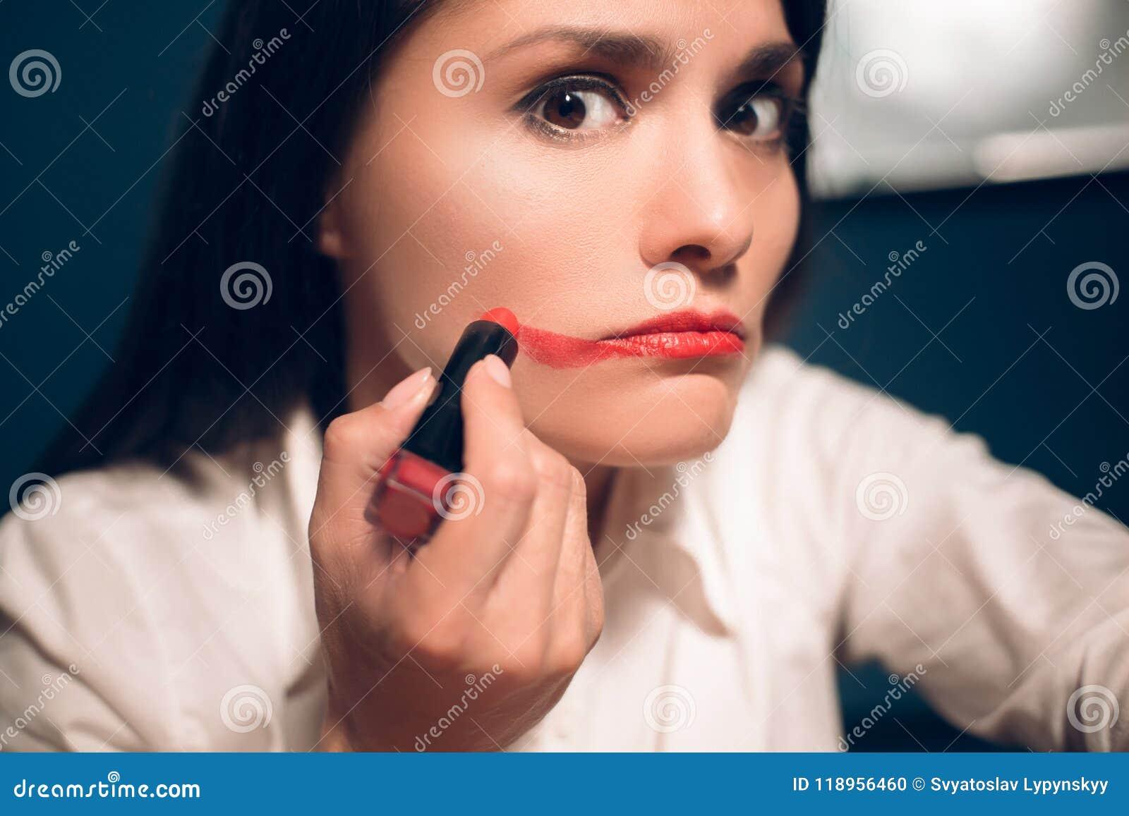 Galen gladlynt kvinna som applicerar läppstift