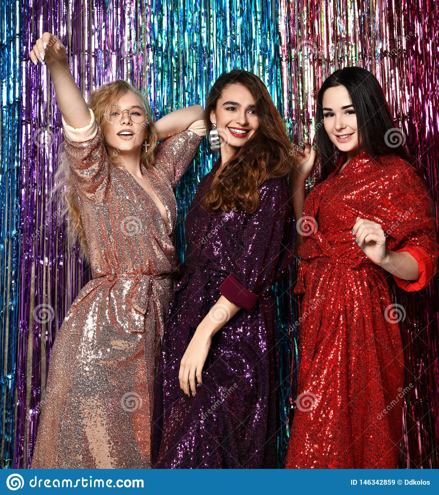 Galen partitid av tre h?rliga stilfulla kvinnor i elegant dr?kt som firar nytt ?r, f?delsedag och att ha gyckel, dans
