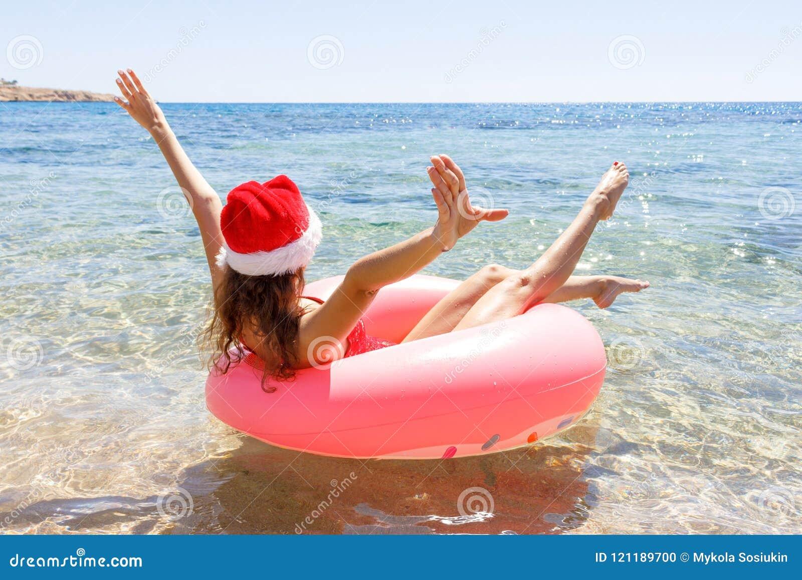 Galen simning med den uppblåsbara munken och julhatten på stranden i solig dag för sommar