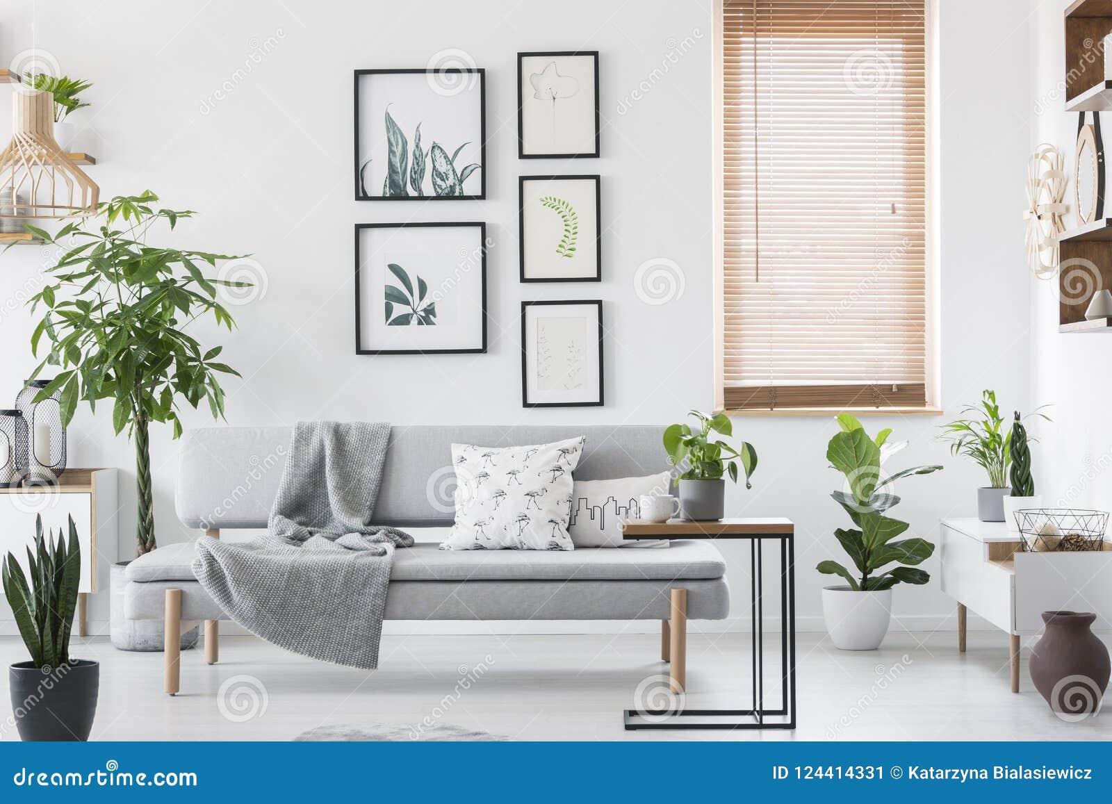 Galerij met installatieaffiches die op muur in echte foto van helder woonkamerbinnenland zo hangen met venster met houten zonnebl