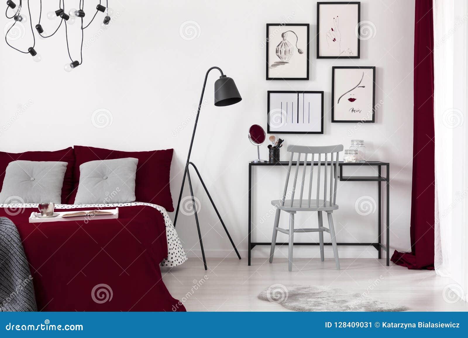 Galerij van illustraties op een witte muur boven een klein bureau dat naast een zwarte metaallamp en een bed van Bourgondië in mo