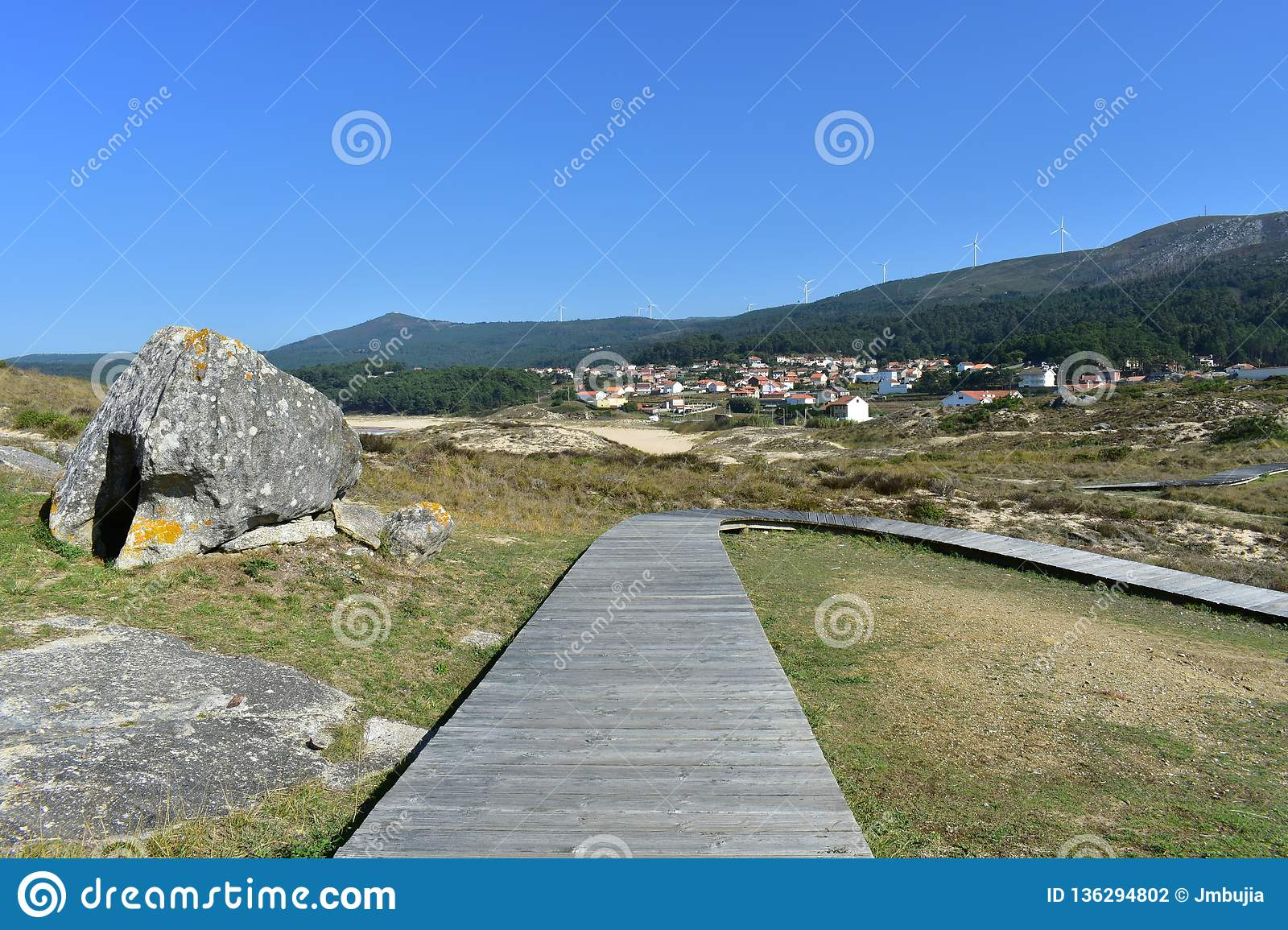 Beach with wooden boardwalk and big sand dunes. Small mountain with forest and coastal village. Blue sky, sunny day. Galicia, Spai