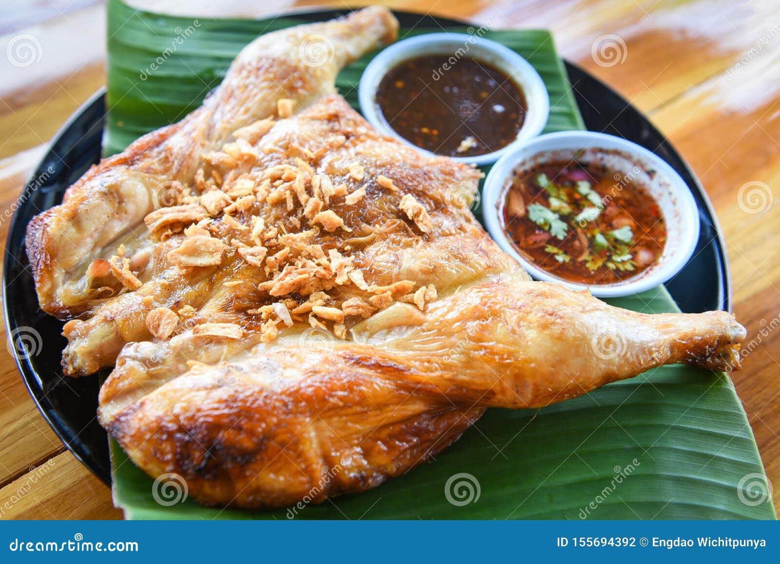 Galinha grelhada com alho e molho picante na placa - o alimento tailandês asiático do estilo grelhou o corpo inteiro da galinha