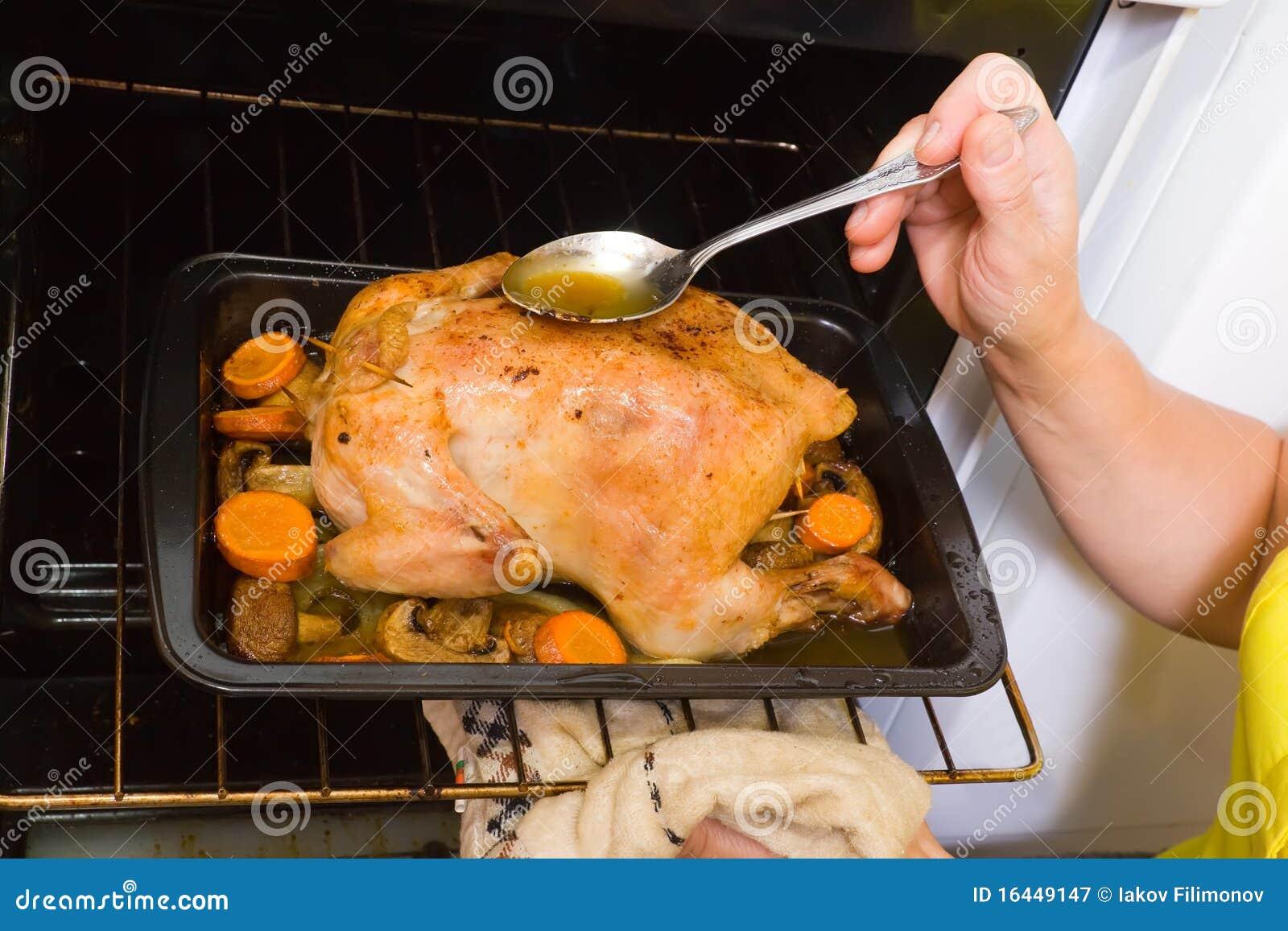 Galinha roasting da mulher no forno