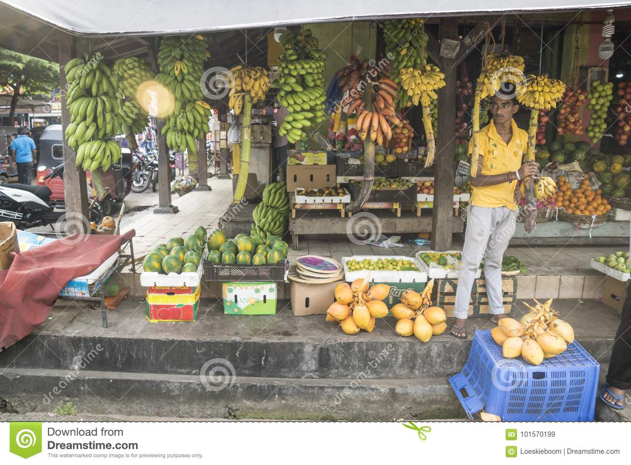 Galle, Sri Lanka - April 11 2017: Market seller standing at a stall with different types of bananas