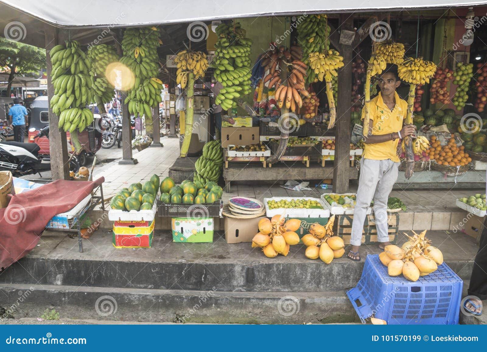 Galle, Sri Lanka - 11 de abril de 2017: Comercialice al vendedor que se coloca en una parada con diversos tipos de plátanos