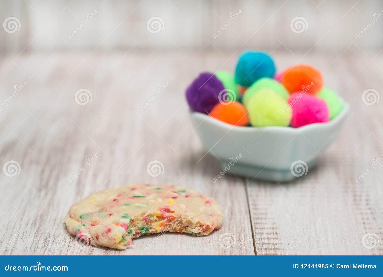 Galleta colorida del confeti mordida con las bolas decorativas