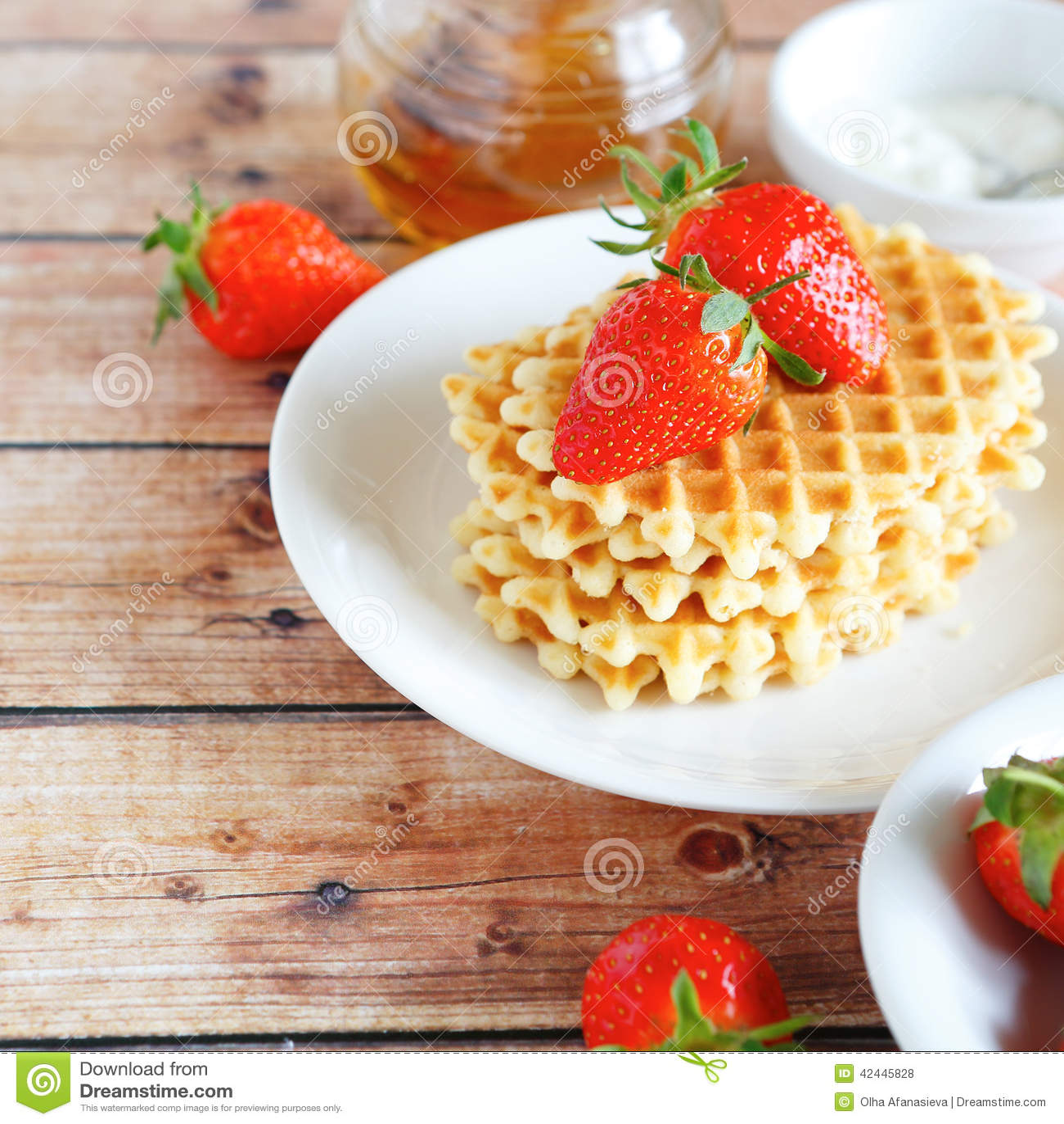 Galletas con las fresas y la crema en una placa