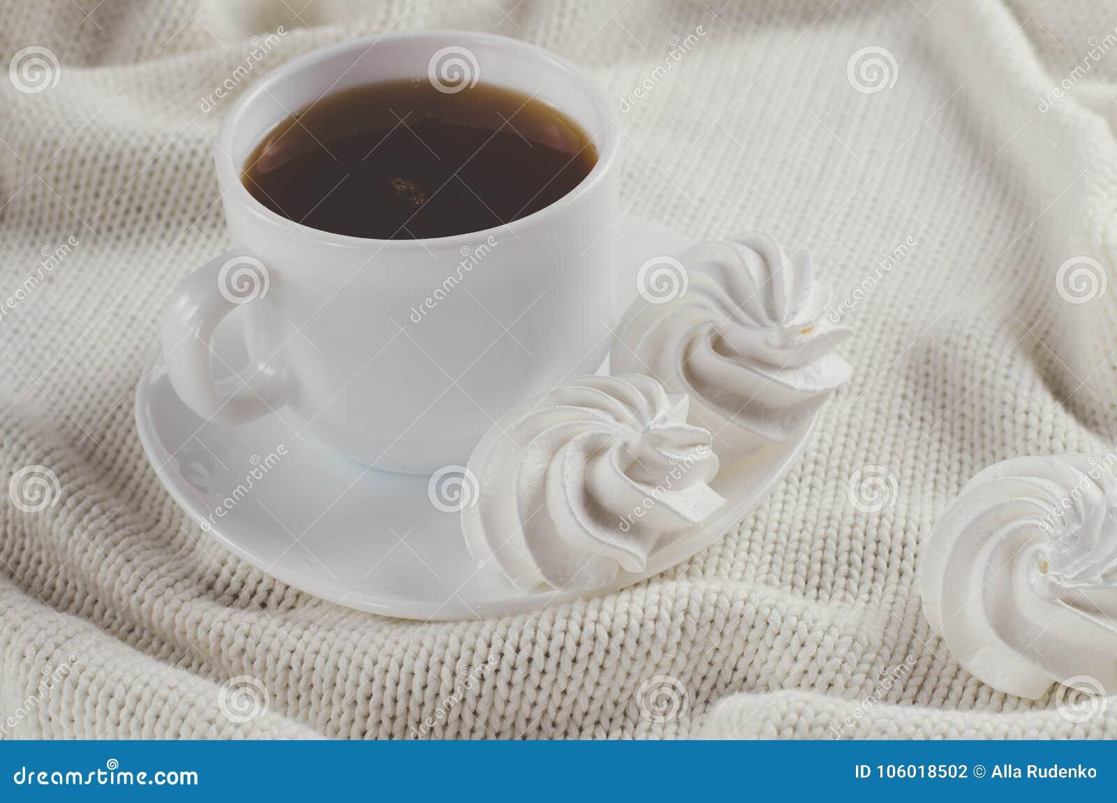 Galletas del merengue y taza deliciosas de té caliente
