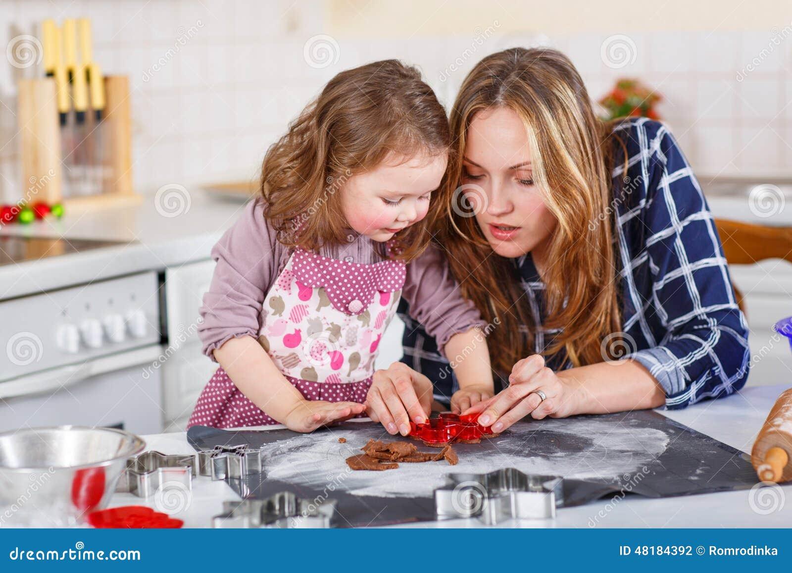 Galletas del pan de jengibre de la hornada de la muchacha de la madre y del niño para la Navidad