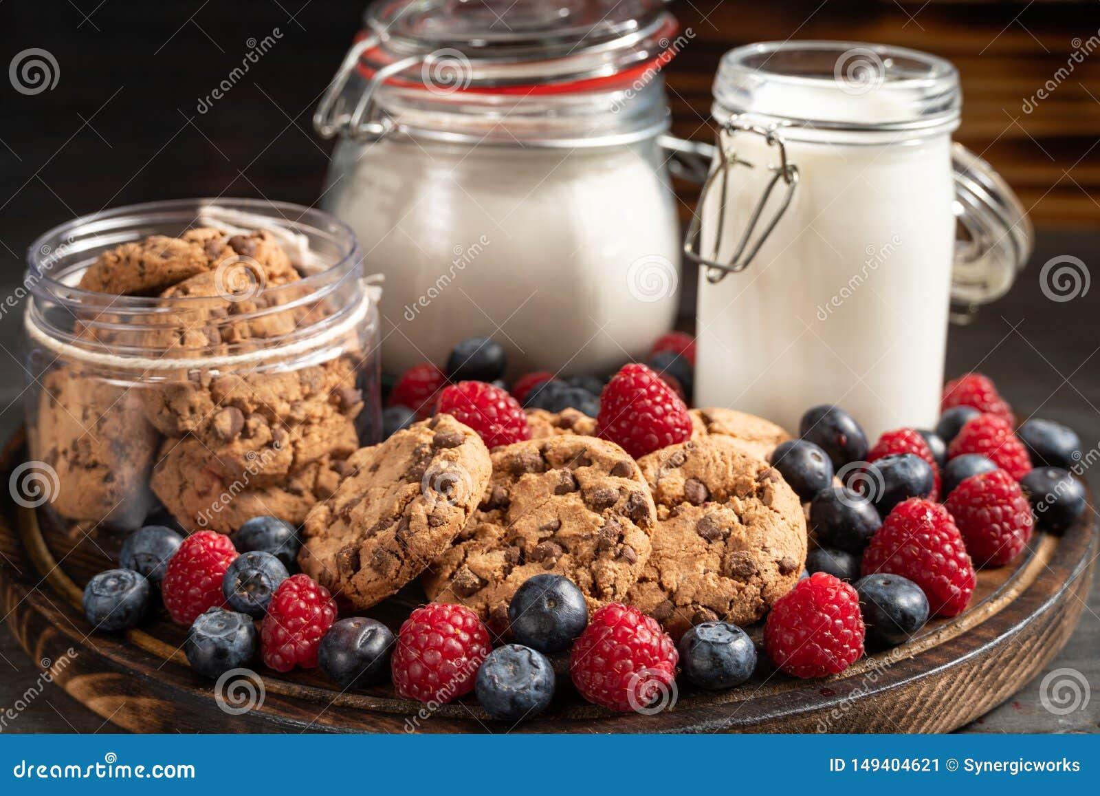 Galletas, leche, beneficiarios de la harina y frutas del bosque colocados en el primer de madera redondeado del disco