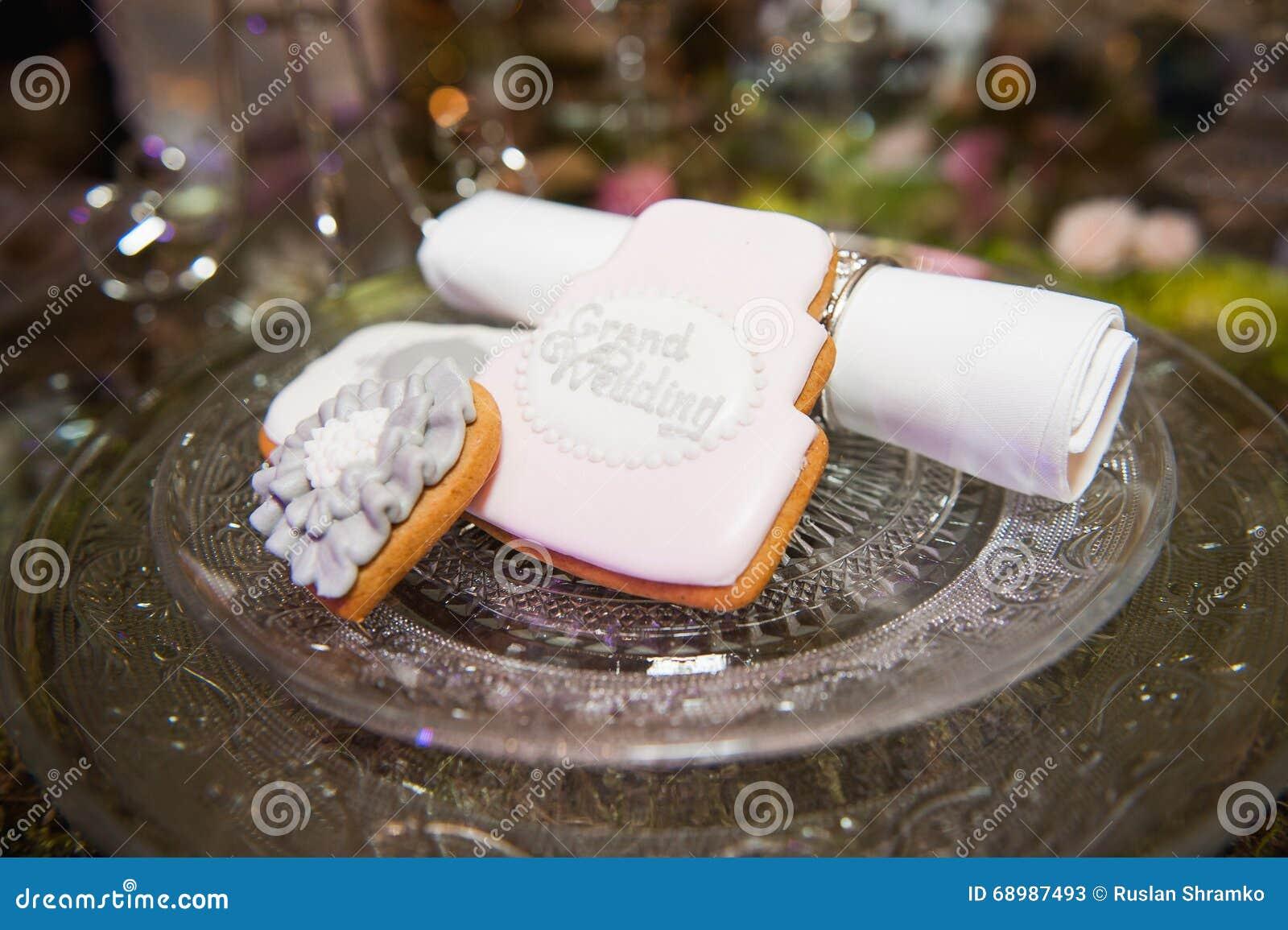 Galletas lindas de la boda en una placa blanca