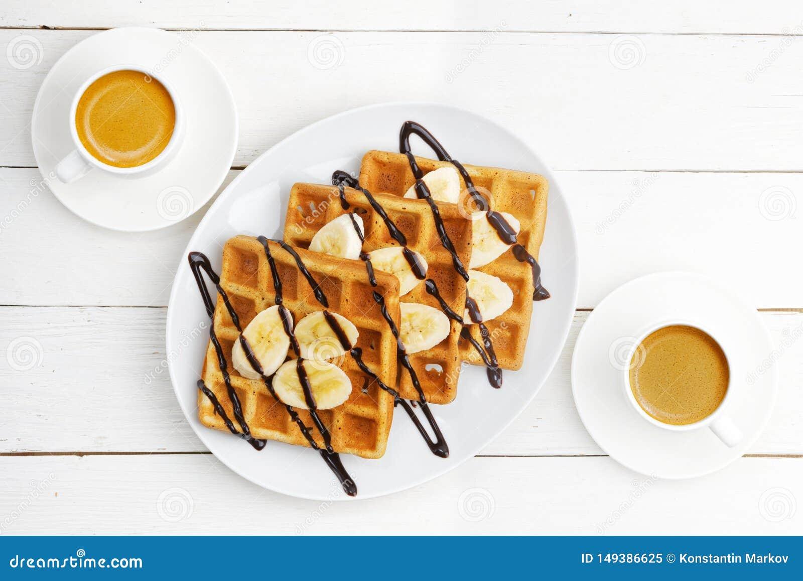 Galletas suaves hechas en casa con las rebanadas del plátano rematadas con el chocolate y dos tazas de café en la tabla de madera