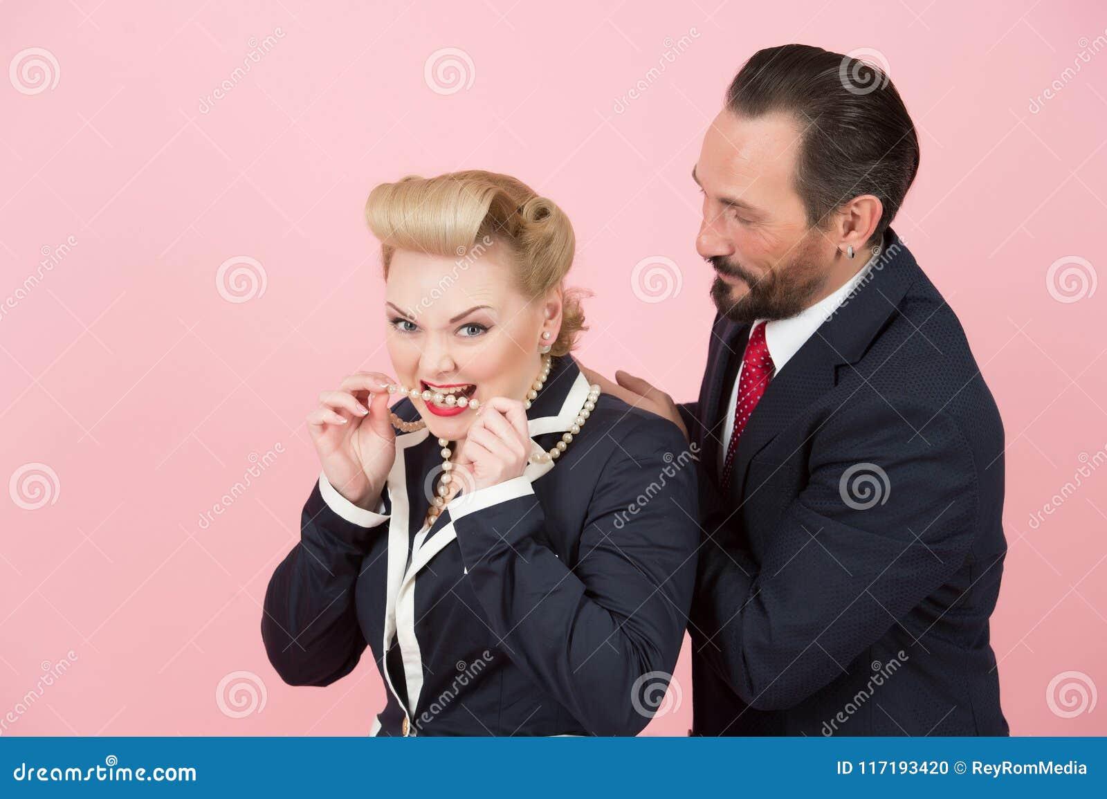 Galna chefer i dräkter och perls Blondinen och framstickandet i rött band har gyckel i studio med perls