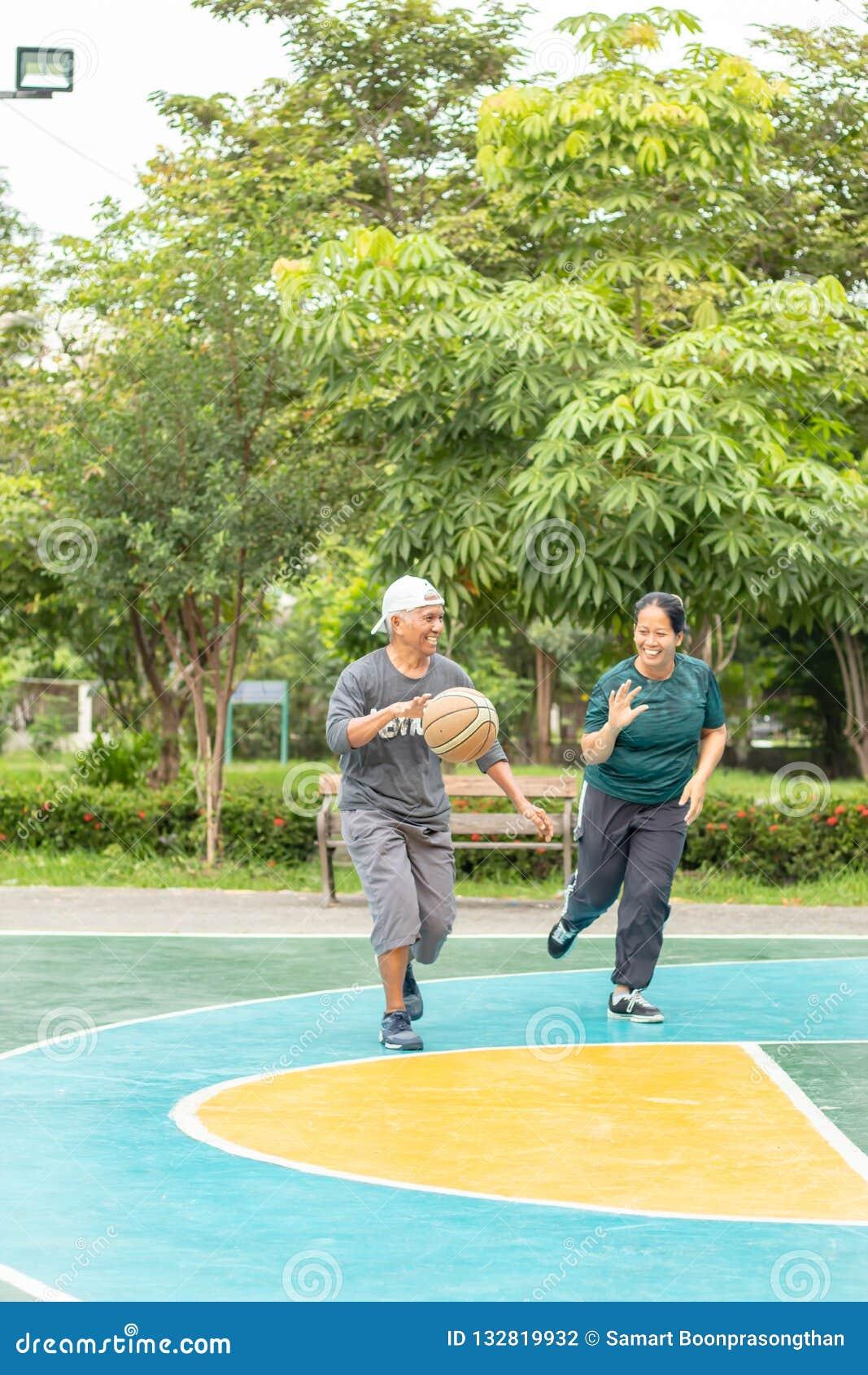Gamal man och kvinna som så lyckligt spelar basket i morgonen