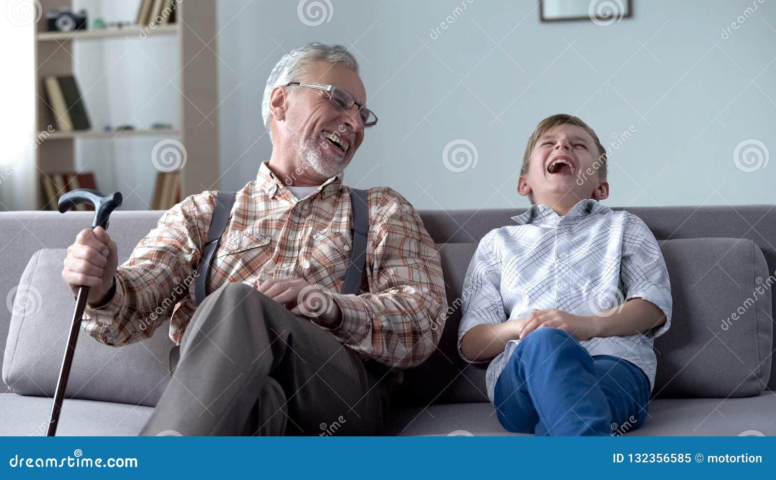 Gamal man och pojke som genuint skrattar och att skoja, värdefulla roliga ögonblick tillsammans
