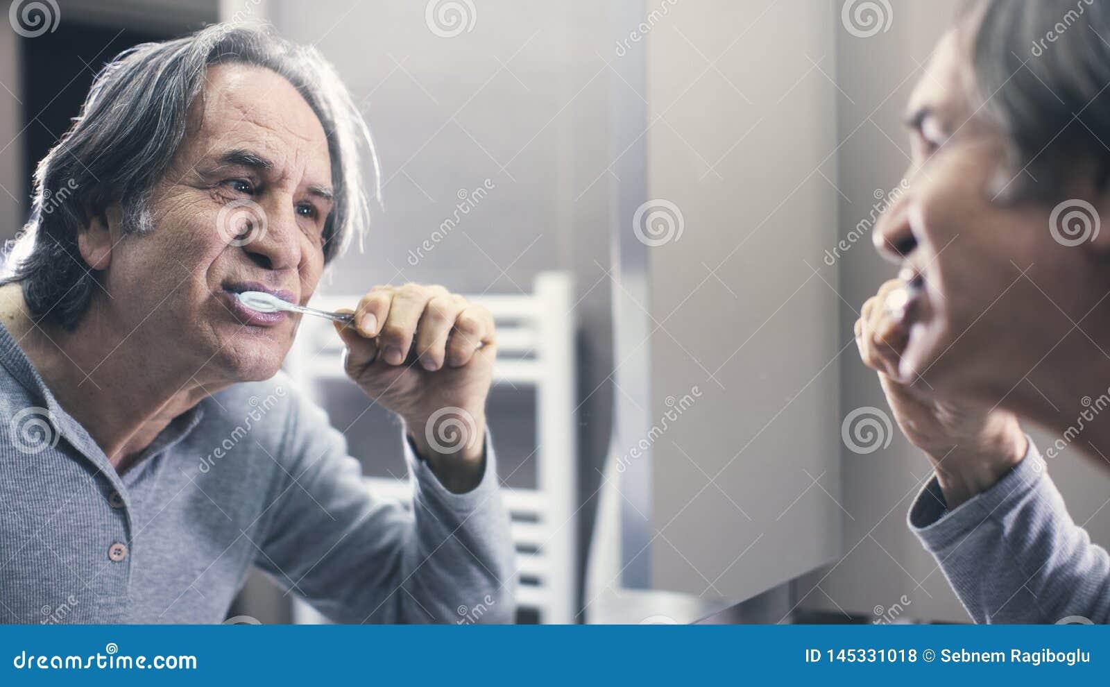 Gamal man som framme borstar tänder av spegeln