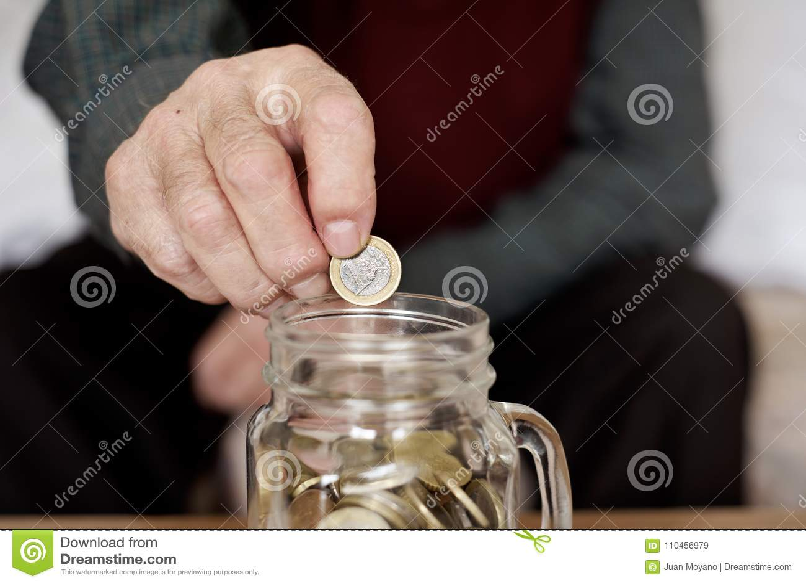 Gamal man som sparar ett ett euro mynt i en glass kruka