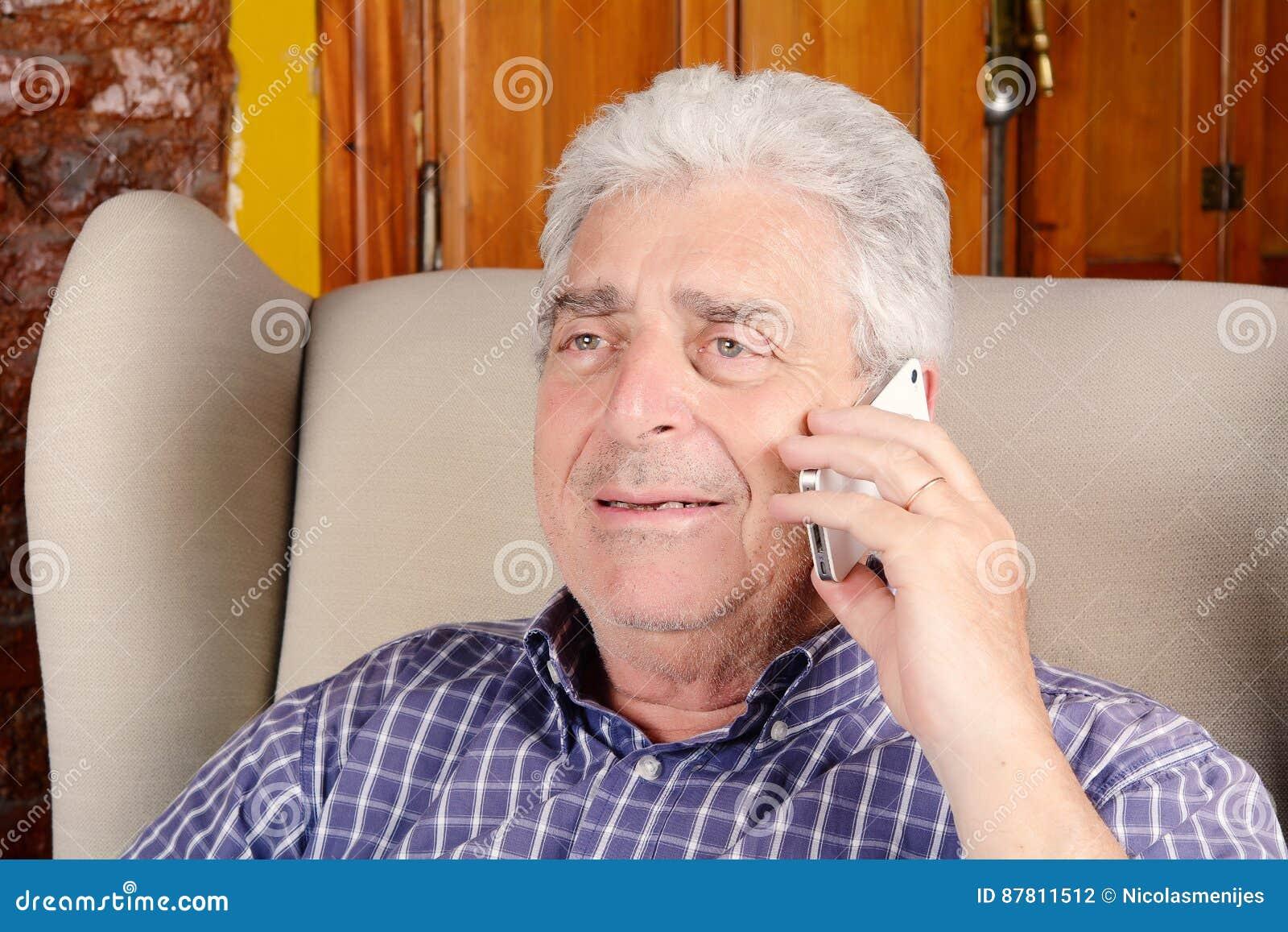 Gamal man som talar på telefonen