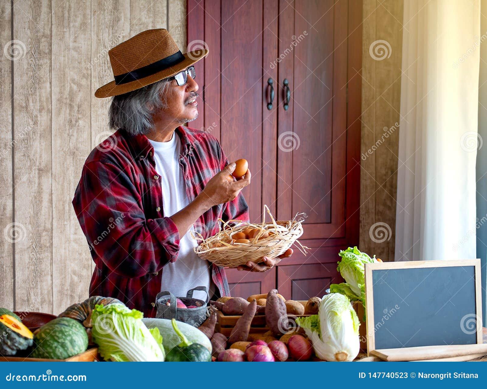 Gamala mannen med hatthållägget och en korg av ägg och blicken till fönstret med dagljus, tänker om hans meny för att laga mat i