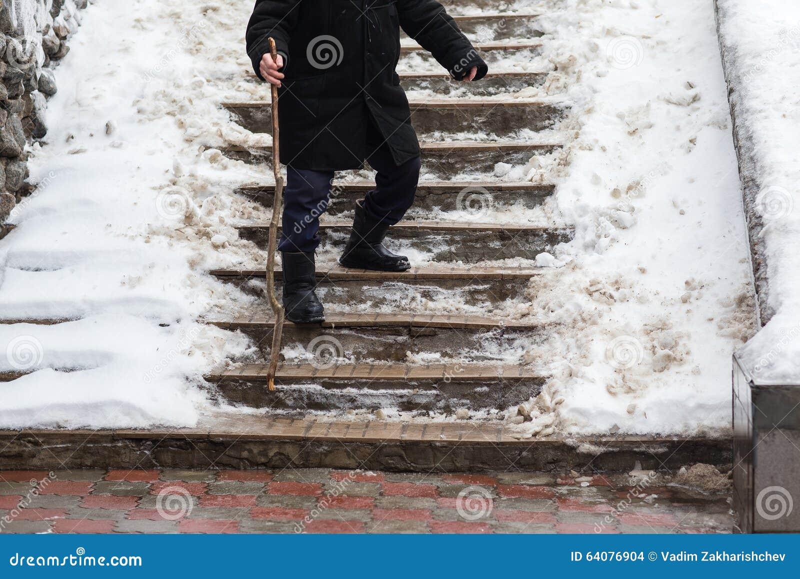 Gamala mannen ner trappan som är hal i vinter