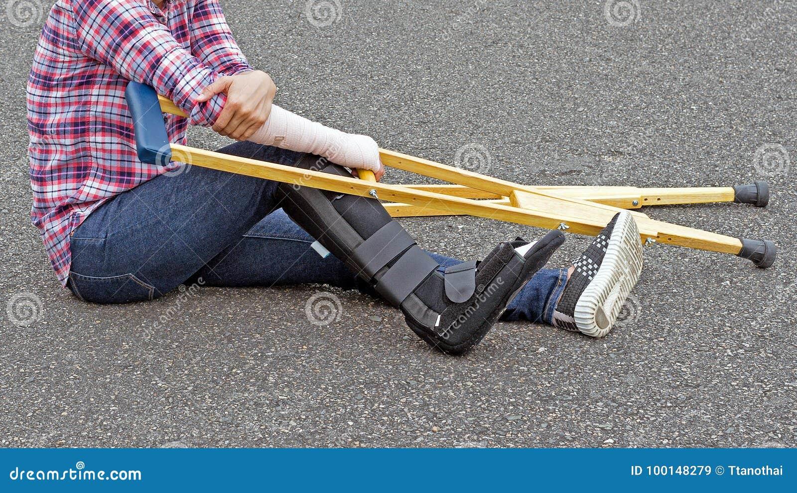 Gamba rotta, camicia della donna di lesione e jeans d uso con lo splin del braccio