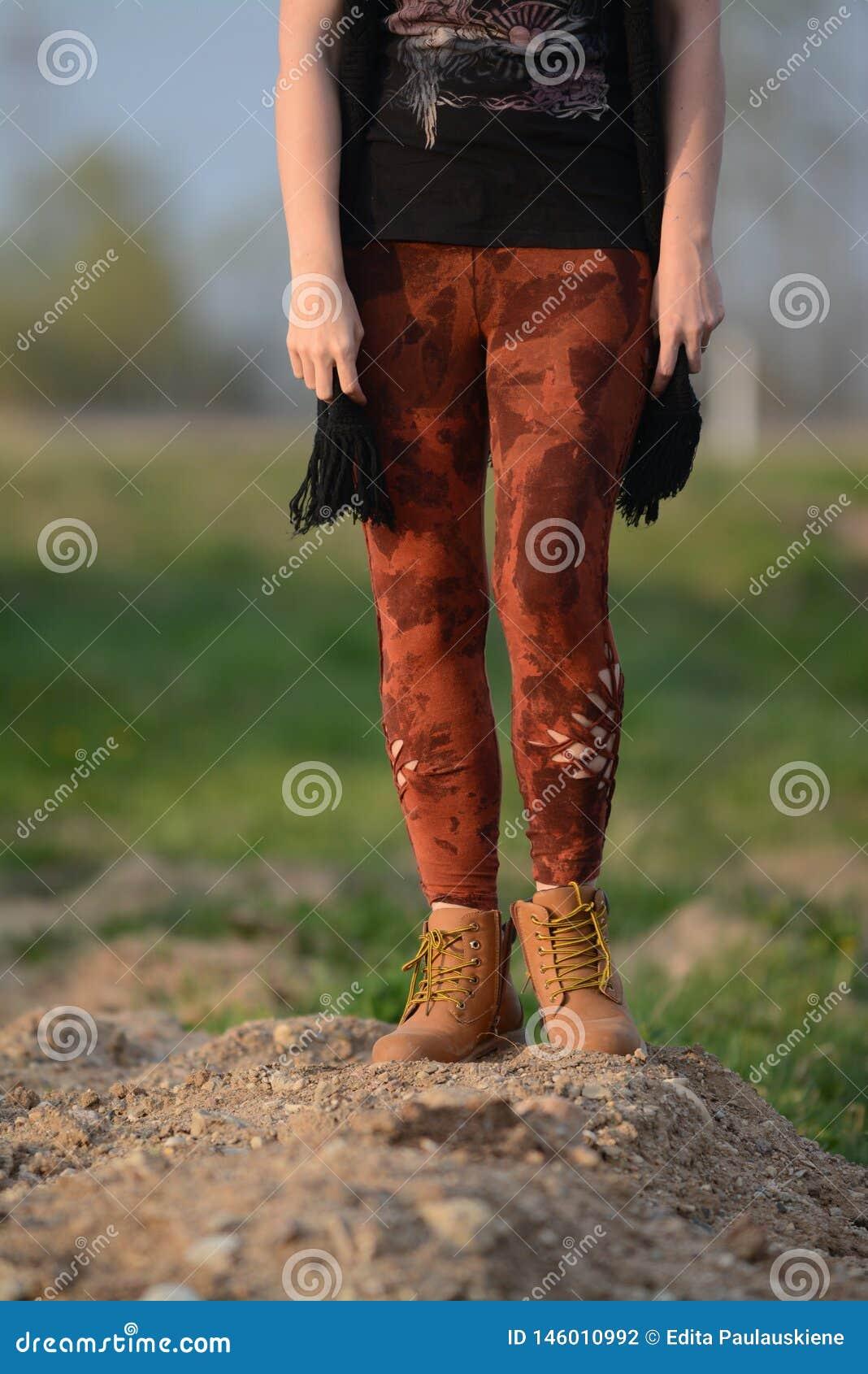 Gambe in belle e calzamaglia tagliate uniche, modo di festival, ora dorata, sera calda