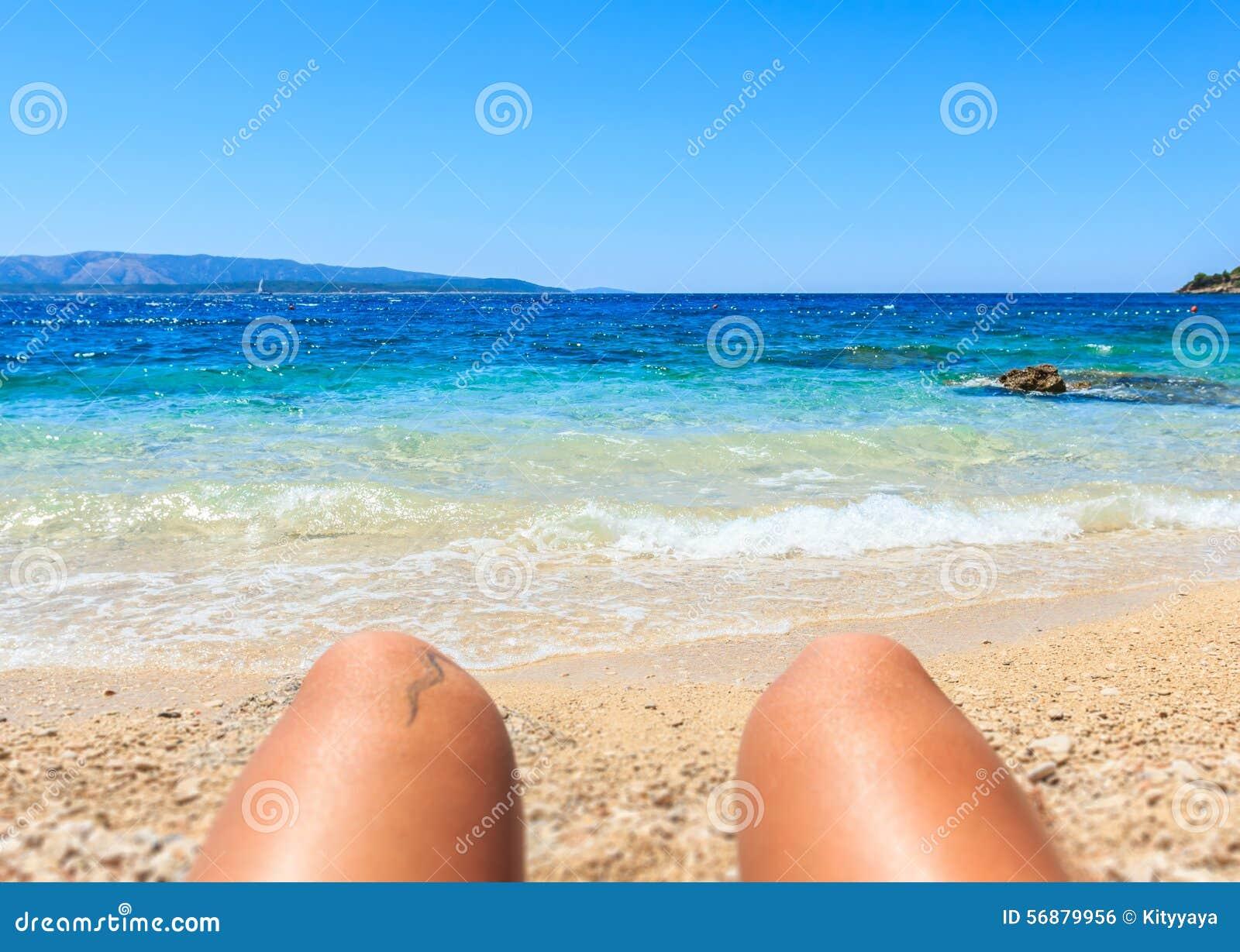 Gambe della donna ed onda del mare sulla spiaggia di sabbia