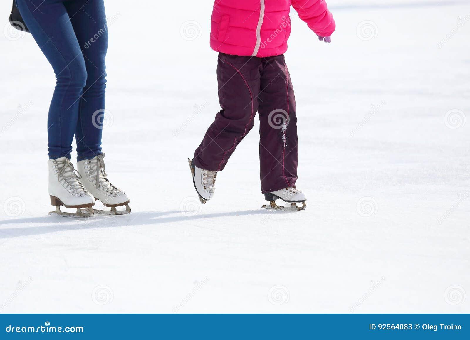 Gambe di un adulto e di un bambino che pattinano sulla pista di pattinaggio sul ghiaccio