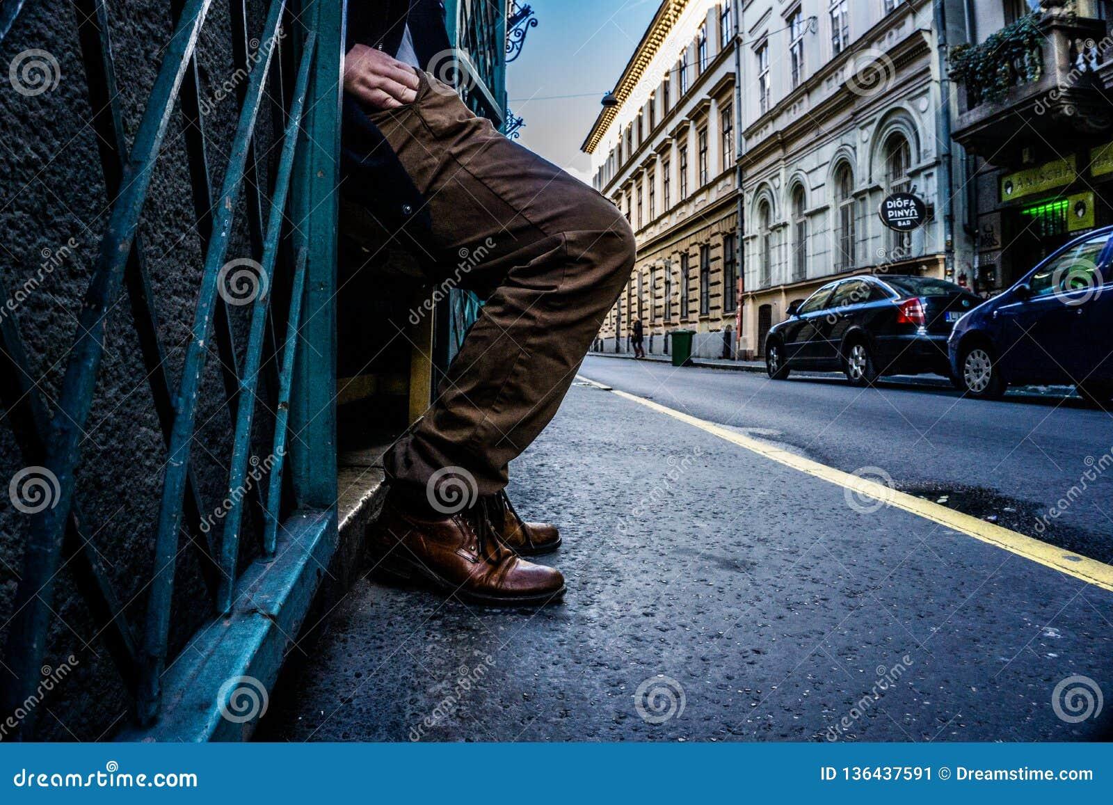 Gambe e mano di un uomo che raggiunge nella sua tasca sulle vie di Budapest, Ungheria con le linee principali che empasizing l at