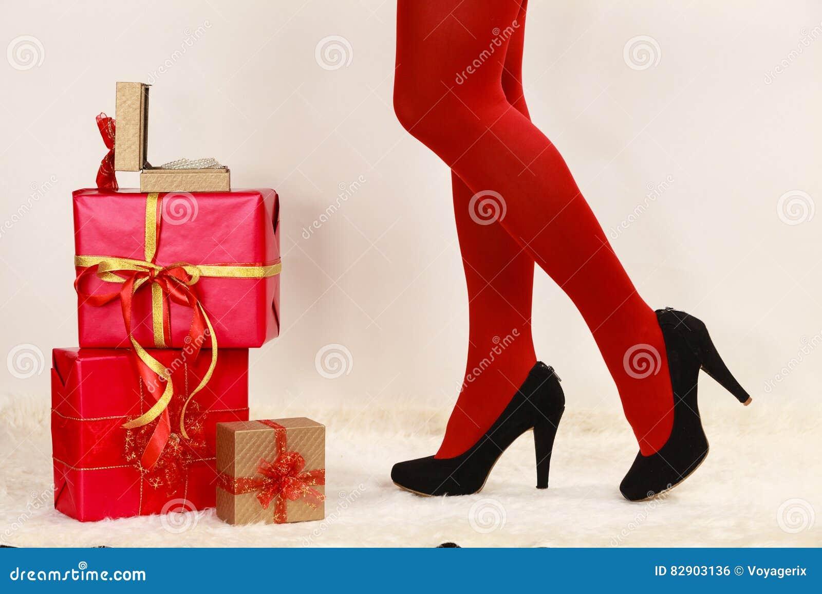 29308c01a2b6 Le gambe lunghe della donna alla moda in collant vivo rosso di colore  anneriscono le scarpe dei tacchi alti con molti contenitori di regalo di  natale su ...