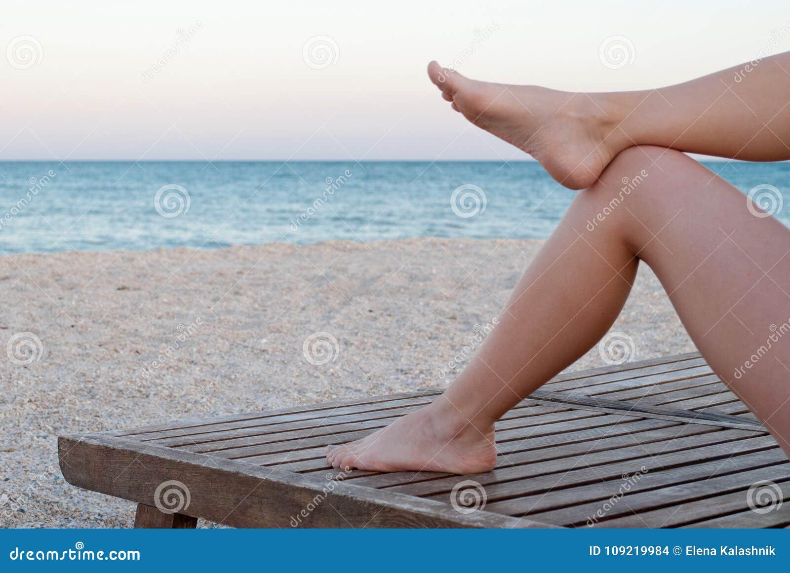 Sdraio Da Spiaggia In Legno.Gambe Snelle Di Una Ragazza Su Una Sedia A Sdraio Di Legno Sulla