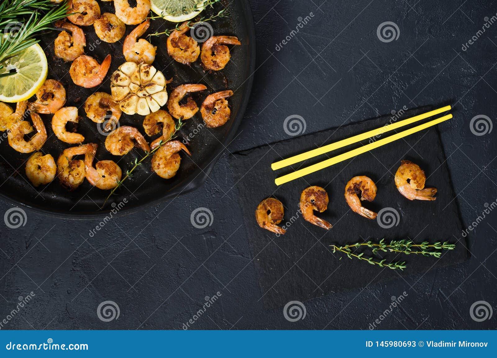 Gamberetti fritti di re in una padella su un fondo nero con i bastoncini gialli